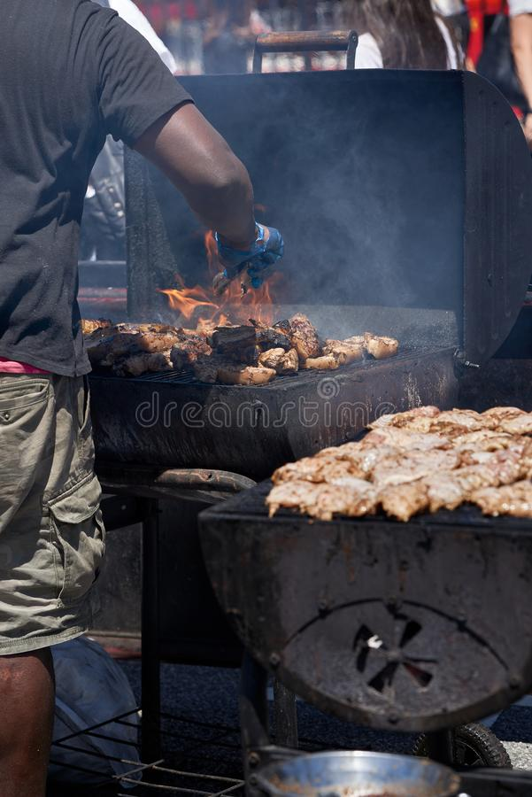 A man manning a flaming barbecue grill cooking meat. Smoke and flames can be seen coming from a barbecue grill full of meat being prepared by a man with royalty free stock photography