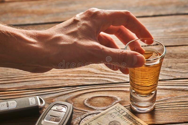 Man& x27; mano de s que alcanza al vidrio con la bebida del alcohol y la llave del coche Concepto de la bebida y de la impulsión imagen de archivo