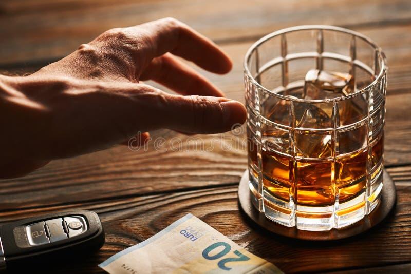 Man& x27; mano de s que alcanza al vidrio con la bebida del alcohol y la llave del coche Concepto de la bebida y de la impulsión fotografía de archivo