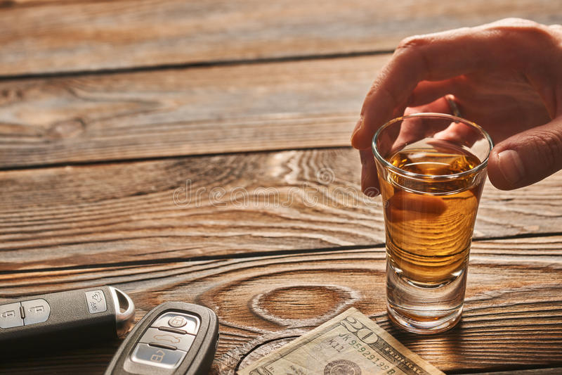 Man& x27; mano de s que alcanza al vidrio con la bebida del alcohol y la llave del coche Concepto de la bebida y de la impulsión foto de archivo libre de regalías