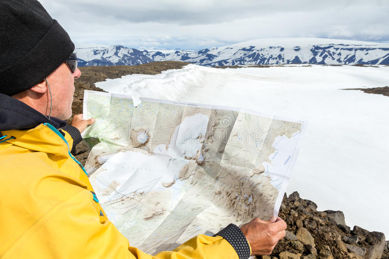 Man with map exploring wilderness on trekking adventure. royalty free stock images