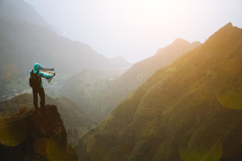 Man with the map staying on top of the mountain rock with gorgeous panorama view over high mountain ranges and deep. Valley royalty free stock photography