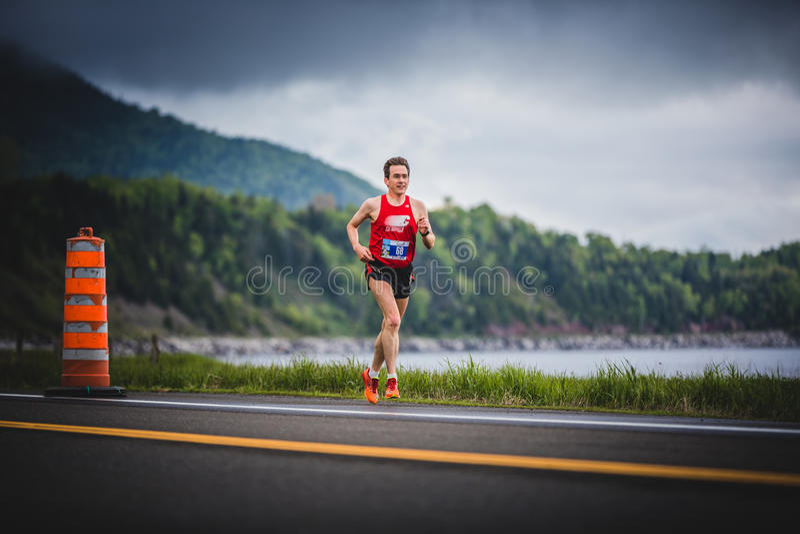 Man Marathoner at about 7km of distance. CARLETON, CANADA - June 4, 2017. During the 5th Marathon of Carleton in Quebec, Canada. Man Marathoner at about 7km of stock photo