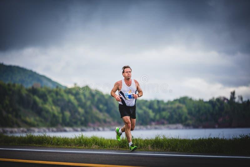 Man Marathoner at about 7km of distance. CARLETON, CANADA - June 4, 2017. During the 5th Marathon of Carleton in Quebec, Canada. Man Marathoner at about 7km of royalty free stock photos