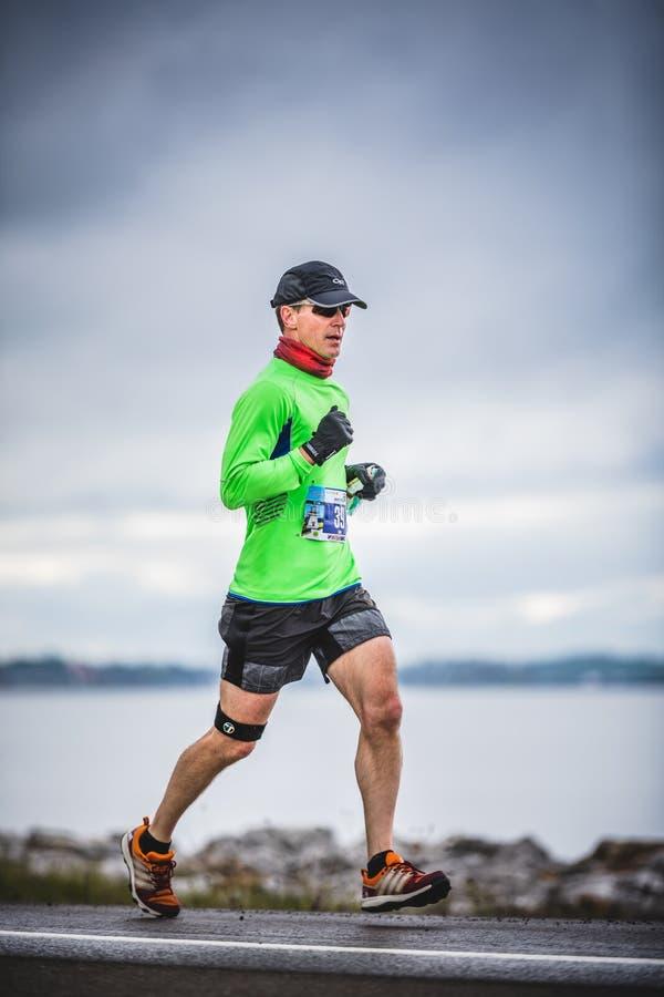 Man Marathoner at about 7km of distance. CARLETON, CANADA - June 4, 2017. During the 5th Marathon of Carleton in Quebec, Canada. Man Marathoner at about 7km of royalty free stock photo