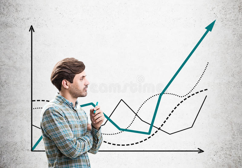Man with marker looks at graphs on concrete stock photos