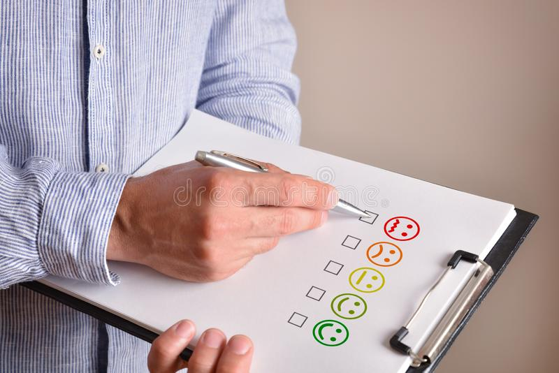 Man marking angry face emoticon drawn on a sheet royalty free stock image