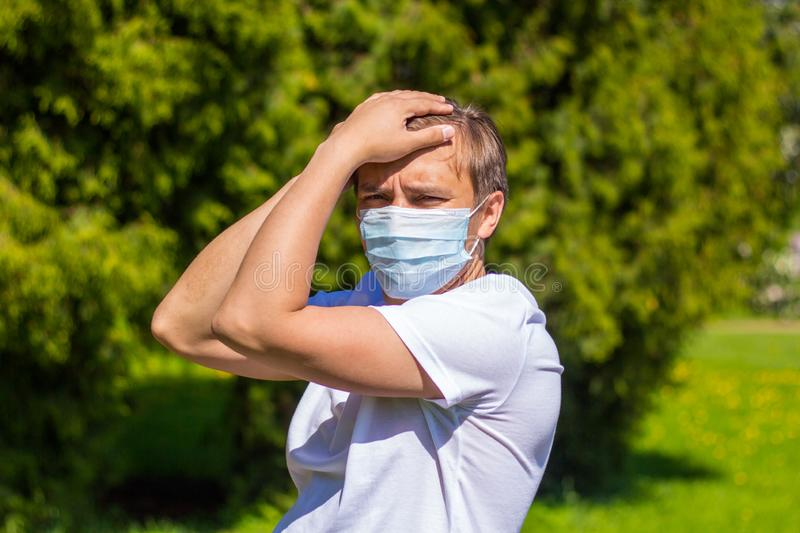 A man in a mask from allergy, in a white T-shirt, stands in the park stock images