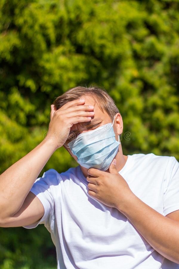 A man in a mask from allergy, in a white T-shirt, stands in the park stock image