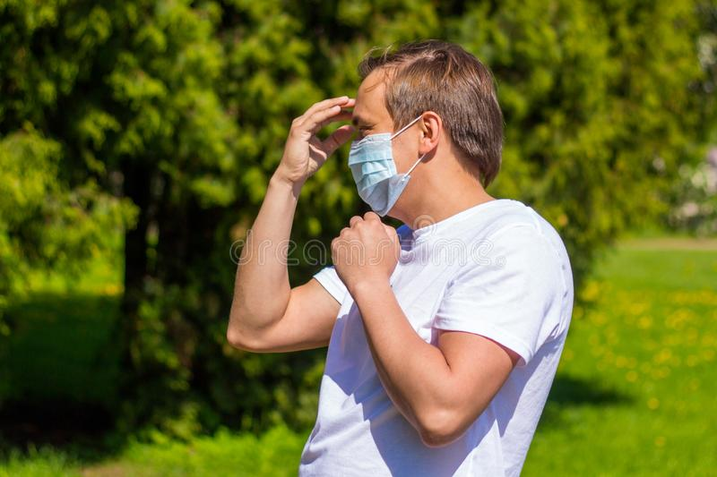 A man in a mask from allergy, in a white T-shirt, stands in the park royalty free stock image