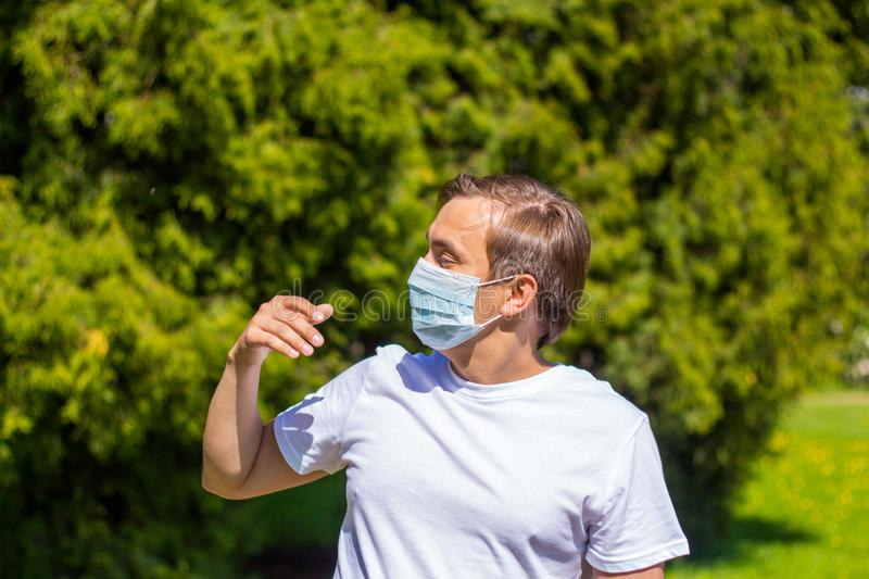 A man in a mask from allergy, in a white T-shirt, stands in the park stock photography