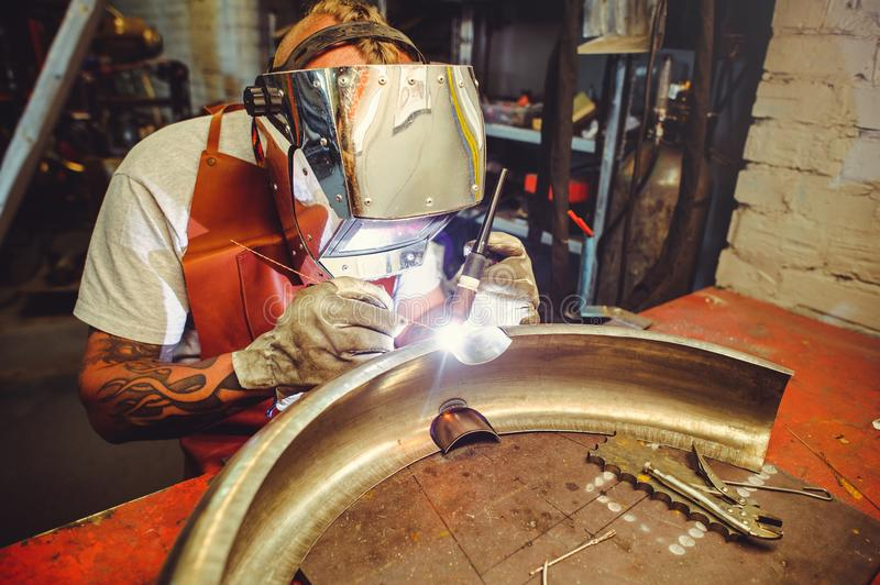 The man in the mask brews beautiful welds with argon-arc welding. Metal stock photos