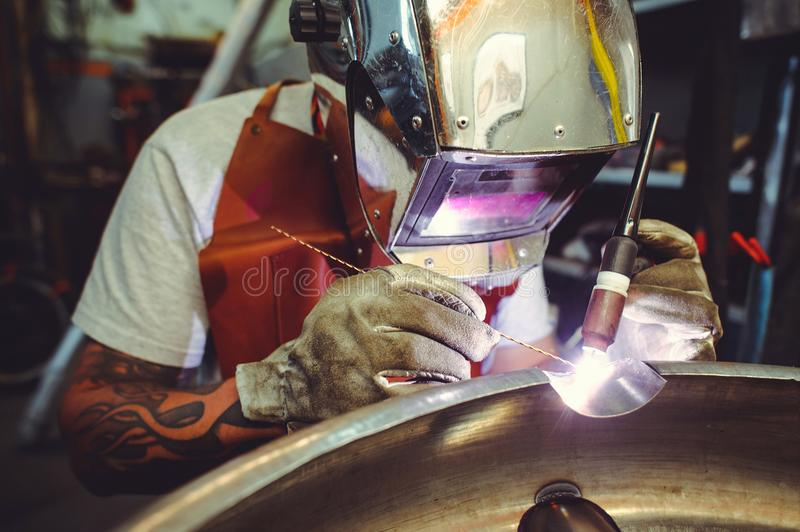 The man in the mask brews beautiful welds with argon-arc welding. Metal stock image