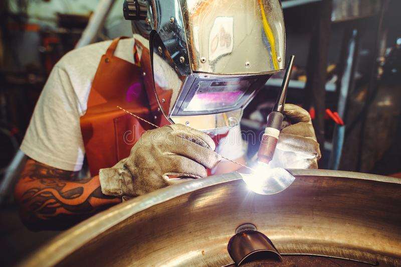 The man in the mask brews beautiful welds with argon-arc welding. Metal stock photo