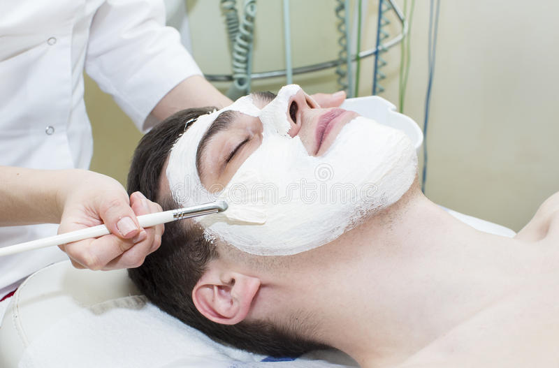 Man in the mask cosmetic procedure. In spa salon royalty free stock image