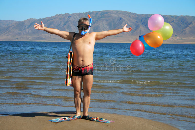 Man with mask, flippers and balloons is salutation. On the beach stock photography