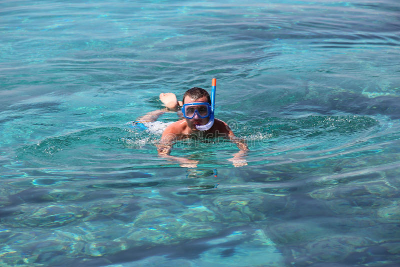 A man in a mask floats in the Mediterranean Sea stock image
