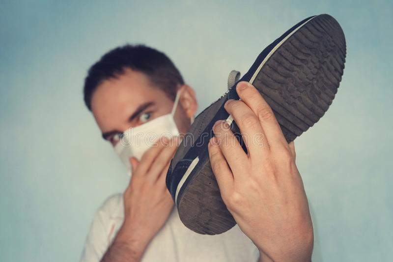 Man with mask is holding dirty stinky shoe - unpleasant smell concept. Dirty smelly sneakers. royalty free stock photos