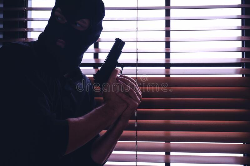 Man in mask holding gun near window. Space for text royalty free stock image