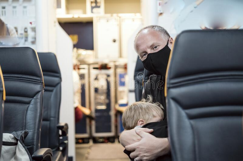 Man in the mask holding his sleeping son in the airplane royalty free stock photography