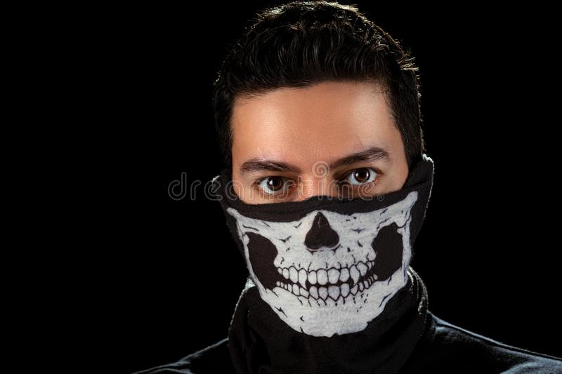 The man in the mask with skull. Closeup portrait of the man with expressive eyes in the mask with skull - anonymous rebel. Isolated on the black background royalty free stock photos