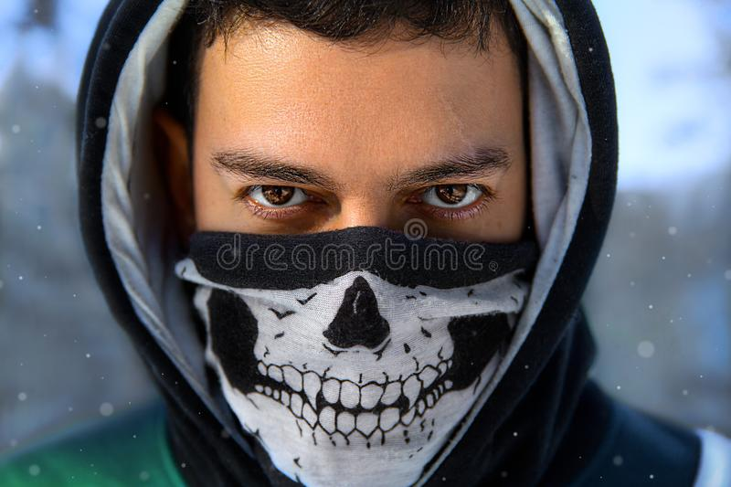 The man in the mask with skull. Closeup winter portrait of the man with expressive eyes in the hood and mask with skull - anonymous rebel stock images