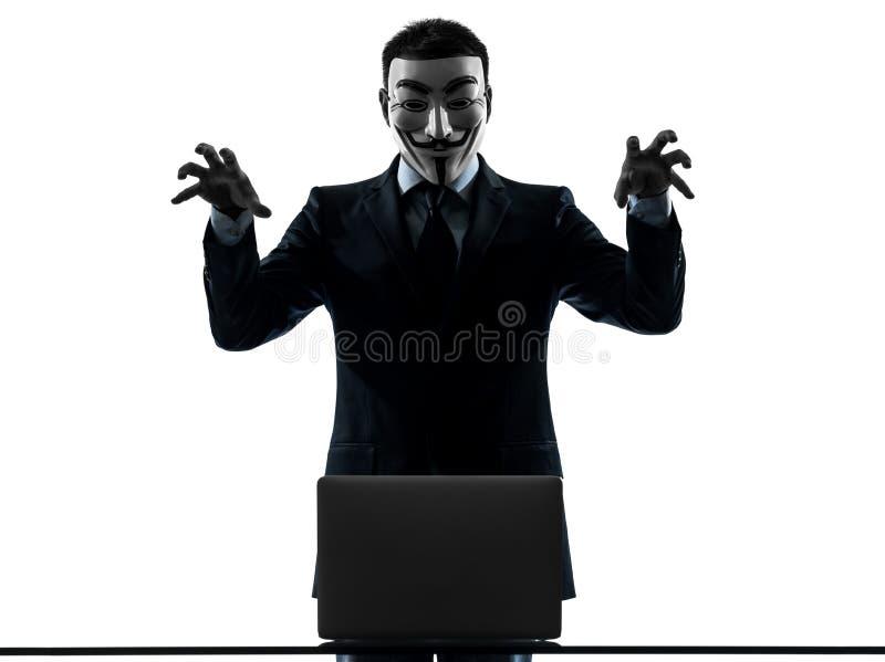Man masked anonymous group member computing computer menacing si. PARIS– OCTOBER 30 : one man dressed and masked as a member of Anonymous underground stock photography
