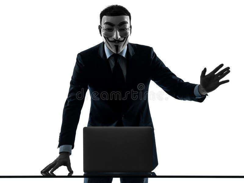 Man masked anonymous group member computing computer saluting si. Paris, France - October 30, 2012 : one man dressed and masked as a member of Anonymous royalty free stock image