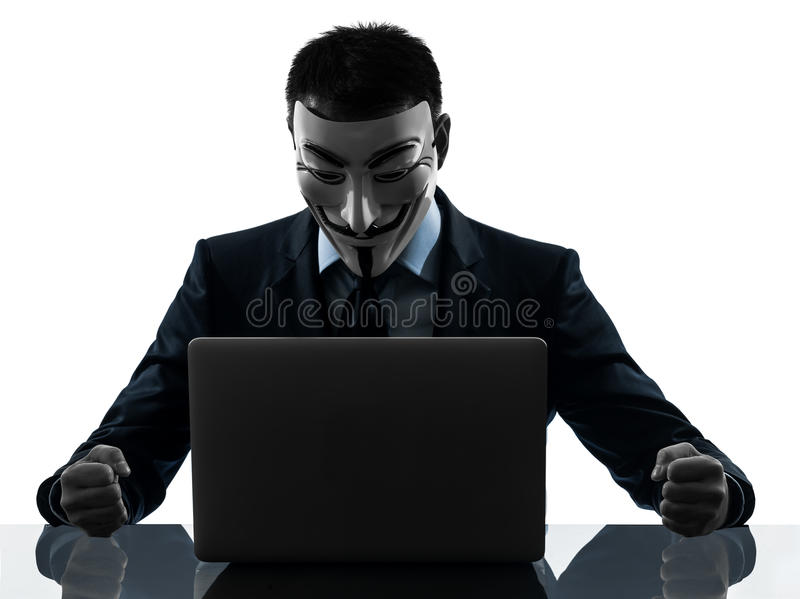 Man masked anonymous group member computing computer silhouette. PARIS– OCTOBER 30 : one man dressed and masked as a member of Anonymous underground group stock photo