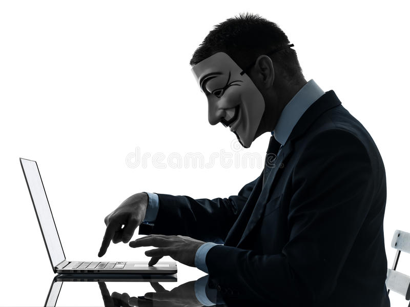 Man masked anonymous group member computing computer silhouette. Paris, France - October 30, 2012 : one man dressed and masked as a member of Anonymous stock photography
