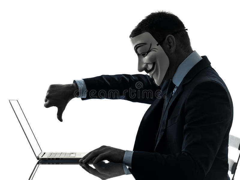 Man masked anonymous group member computing computer silhouette. PARIS – OCTOBER 30 : one man dressed and masked as a member of Anonymous underground royalty free stock images