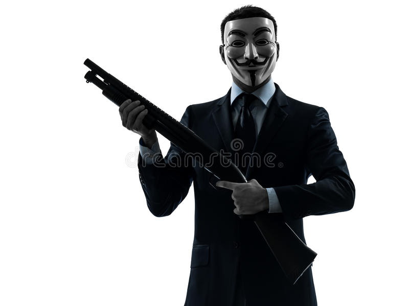"""Man masked anonymous group memeber holding shotgun silhouette po. Paris,€ France -"""" October 30, 2012: one man dressed and masked as a member of Anonymous royalty free stock images"""
