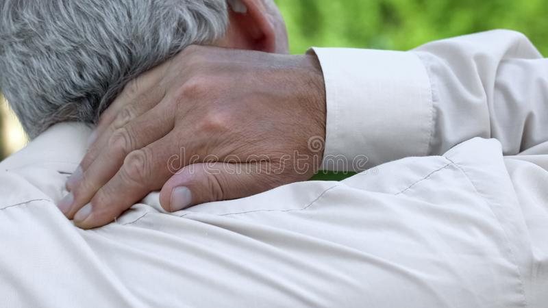 Man massaging numb neck, problems with spine, bad sleep conditions, healthcare stock photos