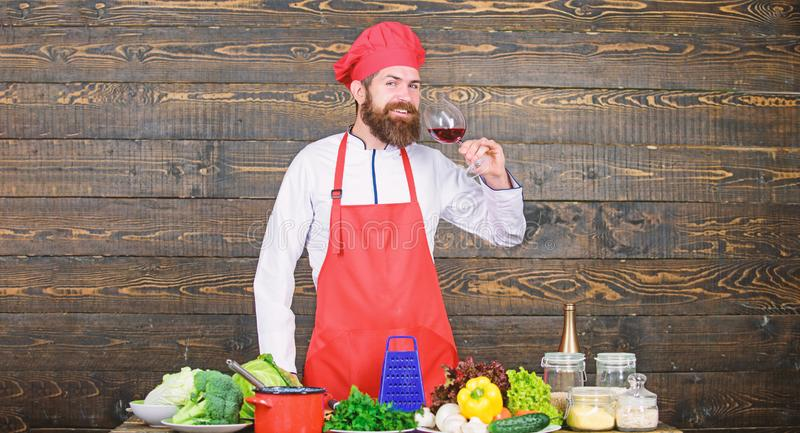 Man master chef hold glass of wine. Which wine serve with dinner. Exquisite dinner concept. Wine degustation. How to. Match wine and food like expert. Hipster royalty free stock photo