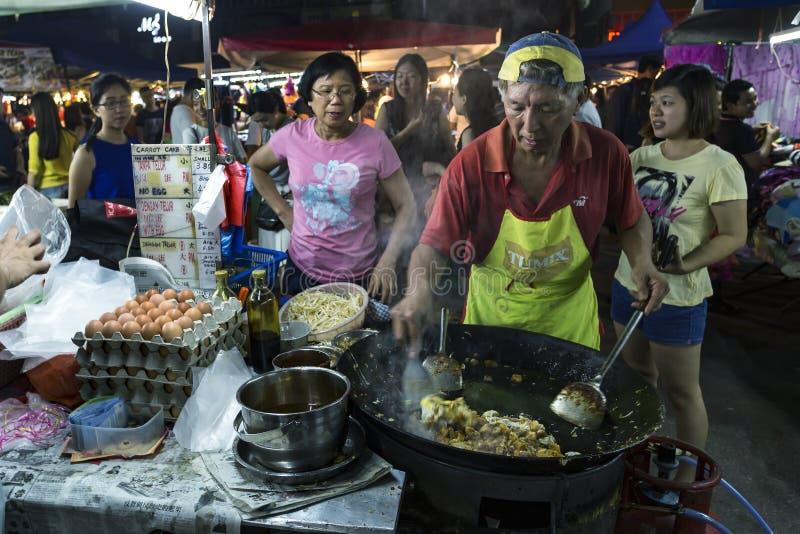 Man matlagningriskakan på PJ Pasar Malam arkivbild