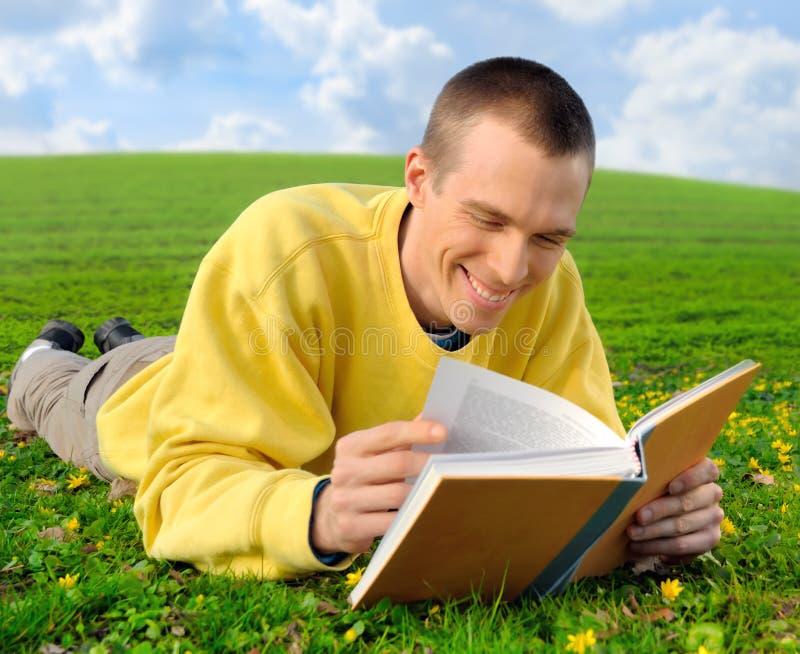 Man on a meadow reading cheerfully stock photos