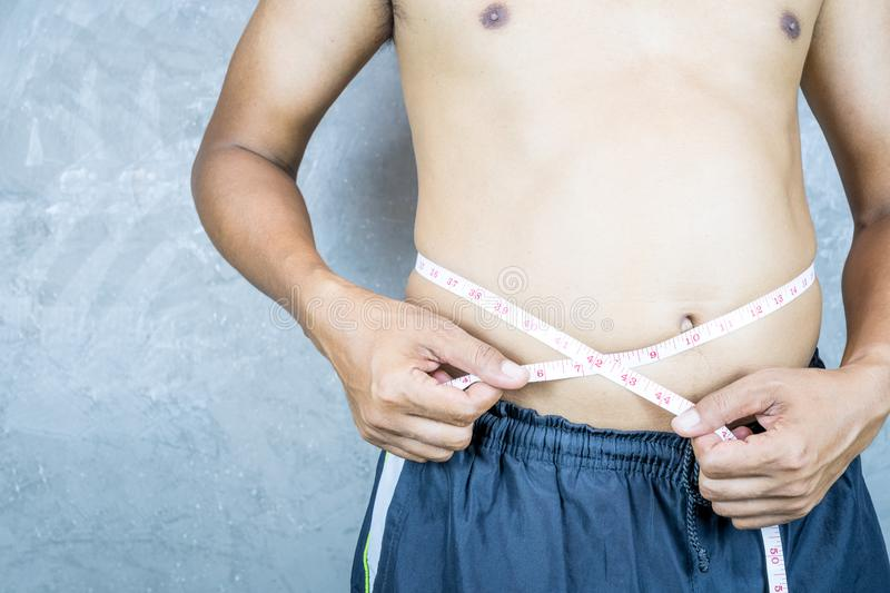 Man measures fat belly with a measuring tape stock photos