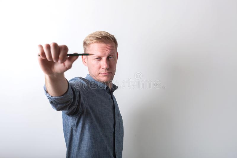A man measures the proportions using a pencil. In a gray shirt on a light background stock image