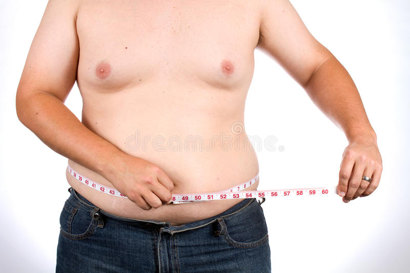 Man Measures Waist. Overweight man uses a fabric tape to measure his waist size royalty free stock photos