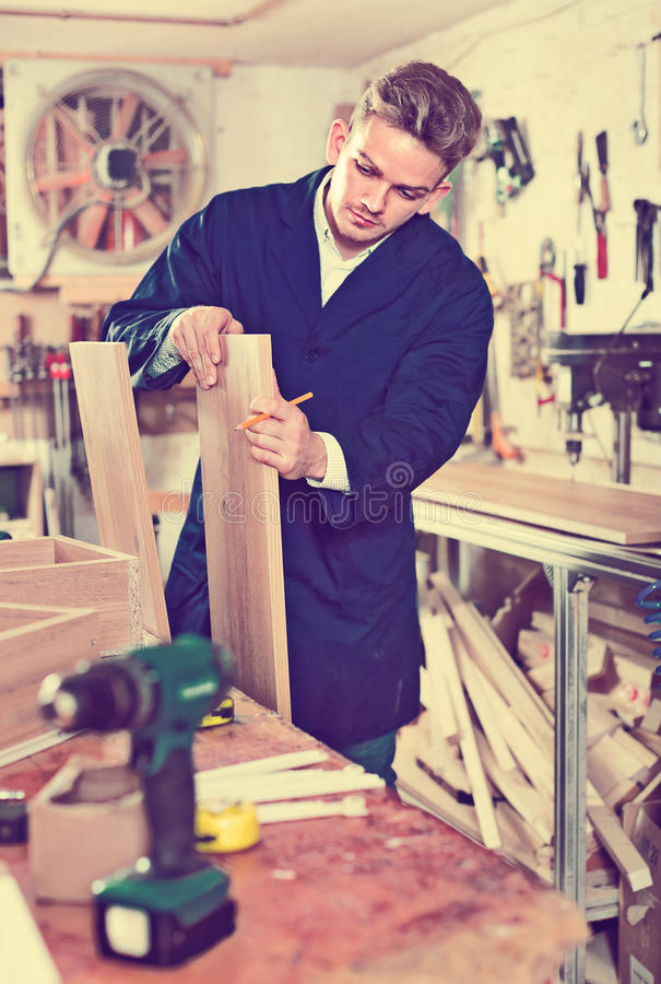 Man measuring boards for furniture at workshop royalty free stock photography