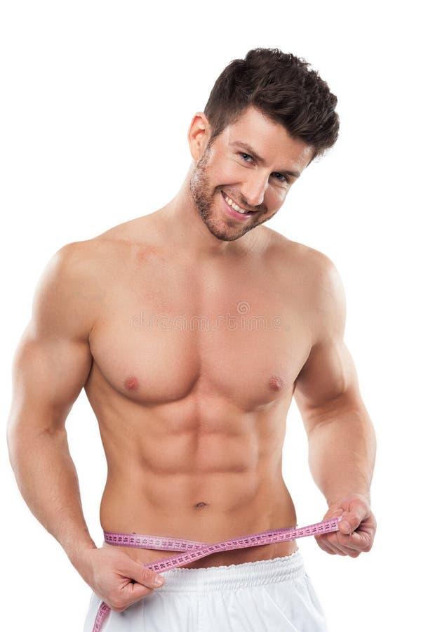 Man measuring his waist royalty free stock photography
