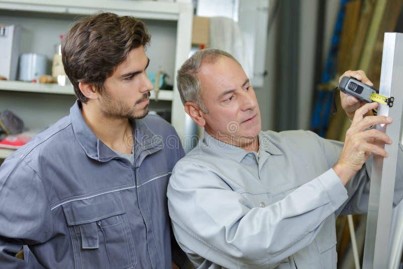 Man measuring width building materials stock photo