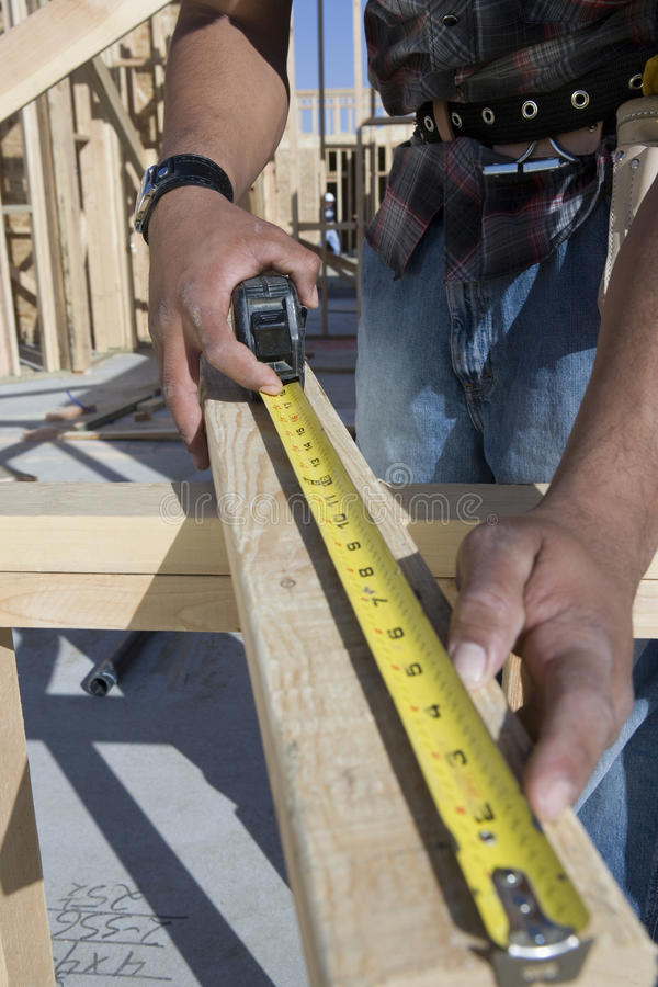 Free Man Measuring Wooden Beam Royalty Free Stock Photography - 29652857