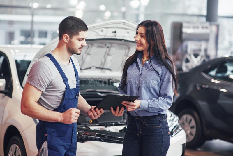A man mechanic and woman customer discussing repairs done to her vehicle stock images
