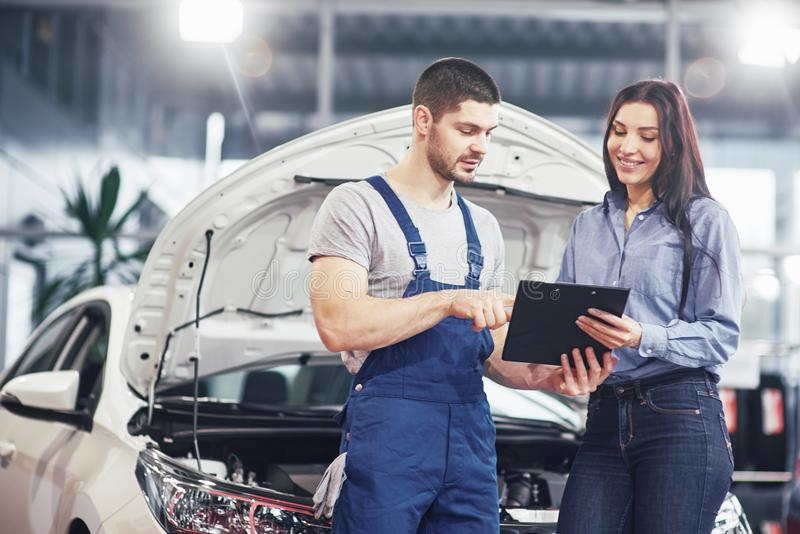 A man mechanic and woman customer discussing repairs done to her vehicle royalty free stock images