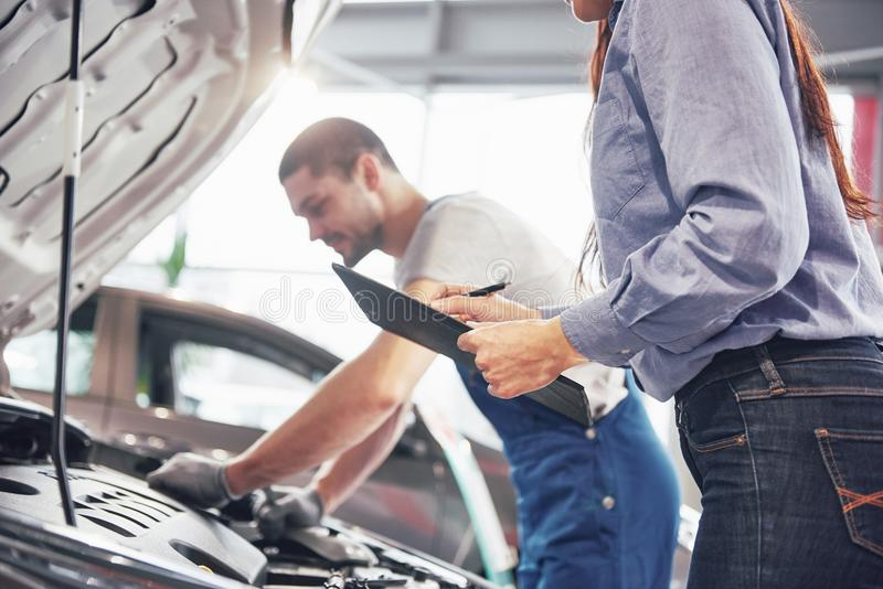 A man mechanic and woman customer look at the car hood and discuss repairs royalty free stock photography