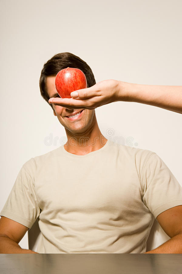 Man med äpplet som är främst av hans framsida arkivbild