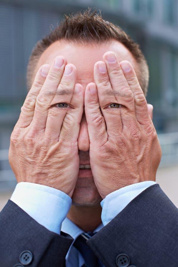Man med ögon på hans händer arkivfoto