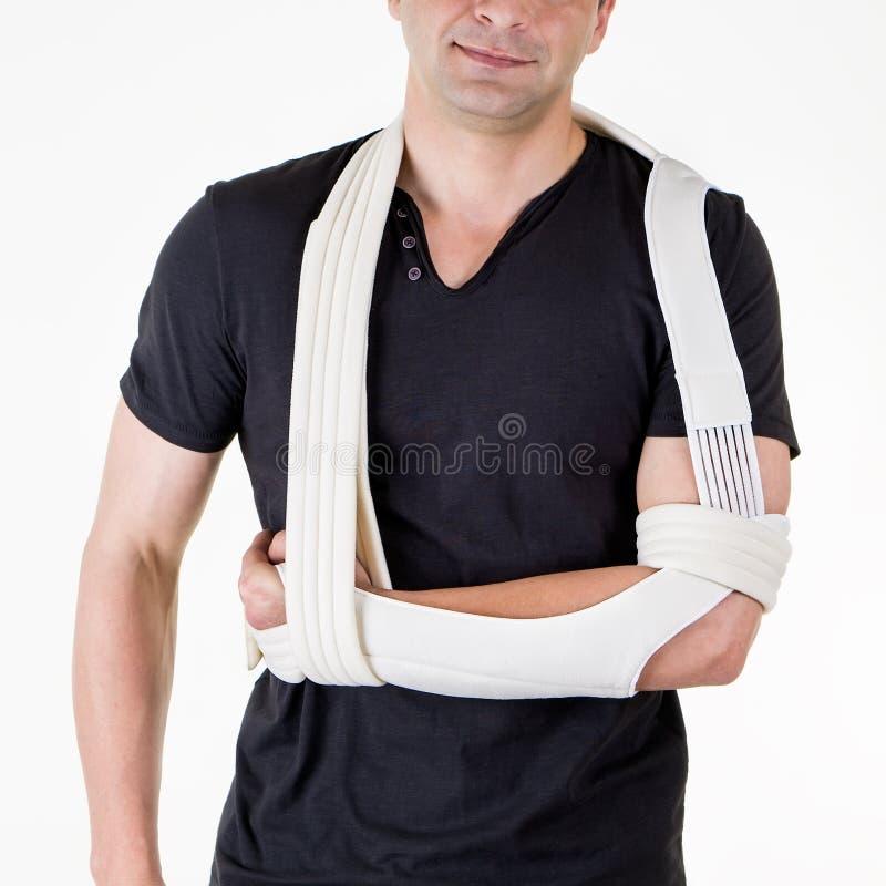 Man med armen som stöttas i rem i den vita studion fotografering för bildbyråer