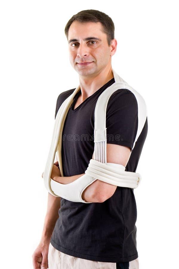 Man med armen som stöttas i rem i den vita studion arkivfoto
